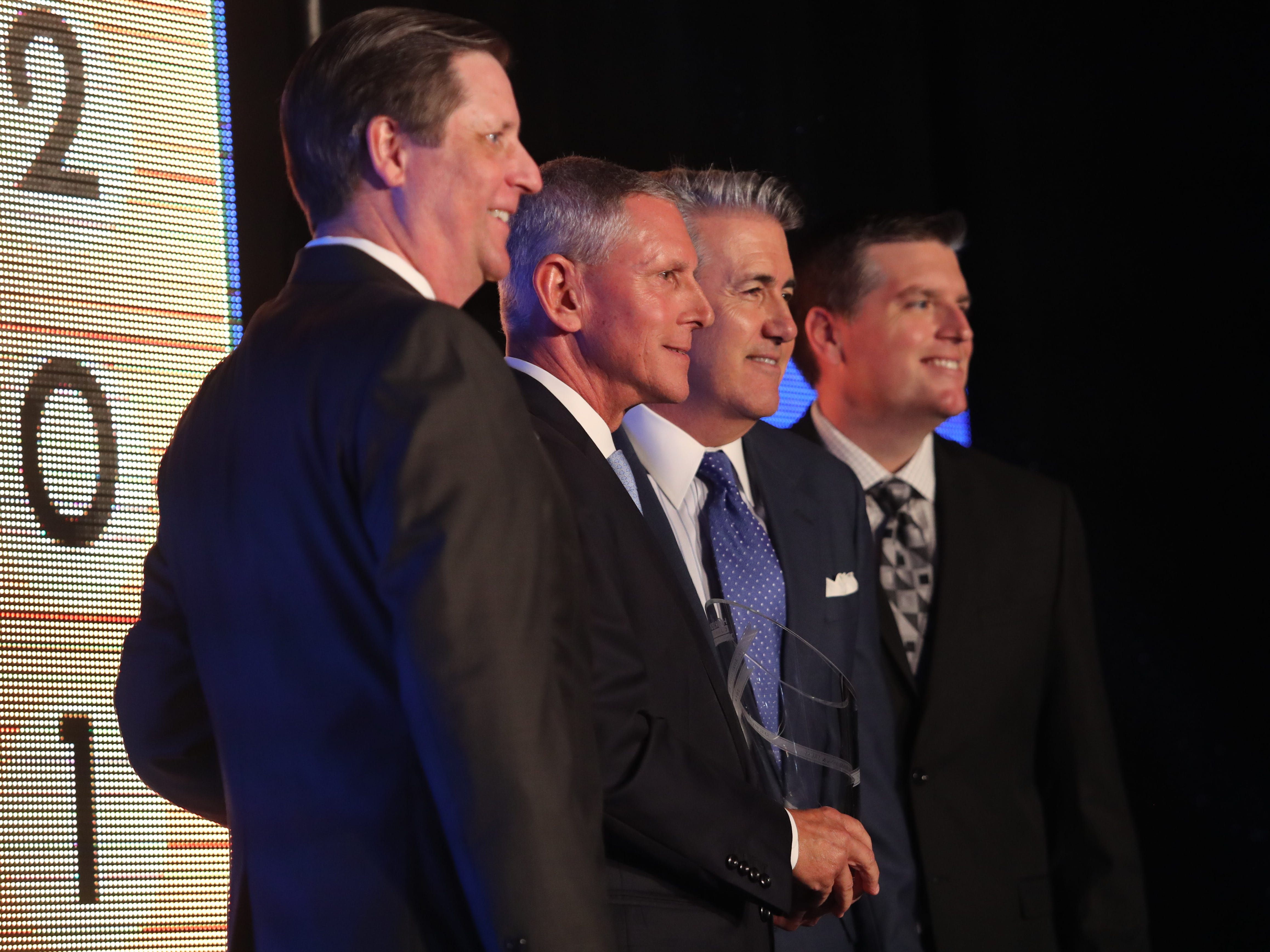 Gray Davis, left, and Lee County commissioner Brian Hamman, right,  present Joseph Catti and Harlan Parrish, of FineMark National Bank, the award for Business of the Year at the 2018 Industry Appreciation Awards on Thursday at the Hyatt Regency Coconut Point Resort and Spa in Bonita Springs.