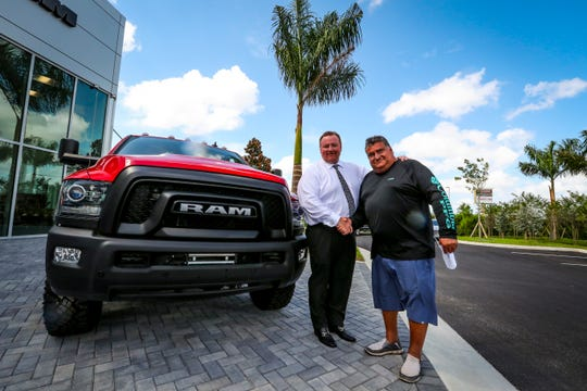 "The new Cape Coral Chrysler Dodge Jeep Ram dealership has opened. The first sale went to Chuck Cordisco, a friend of the dealership general manager Jay Ganzi, who purchased a new, red Dodge Ram 2500 ""Power Wagon"" 4 x 4. The two shake hands."