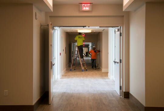 Drywall installers work on the interior finishes in the independent living apartment building at Amavida on Tuesday, October 2, 2018, in south Fort Myers.