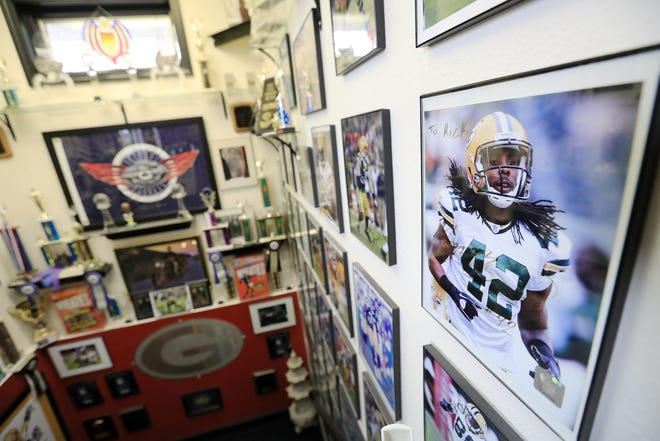 Signed photos of athletes tattooed by Rick Harnowski, including many Green Bay Packers players, are displayed alongside Harnowski's awards in his shop, Tattoos by Rick on Military Avenue.
