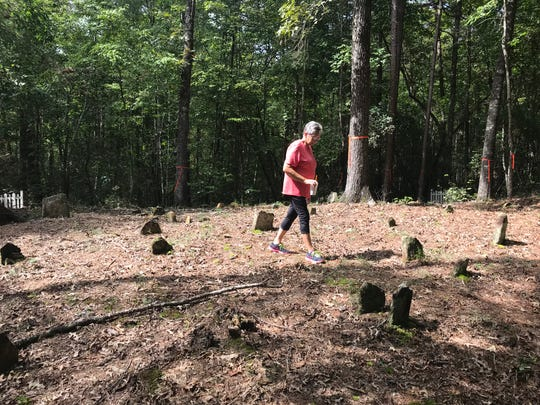 Helen Winchester Dodgens walks across her family's ancestral cemetery in Pickens County.