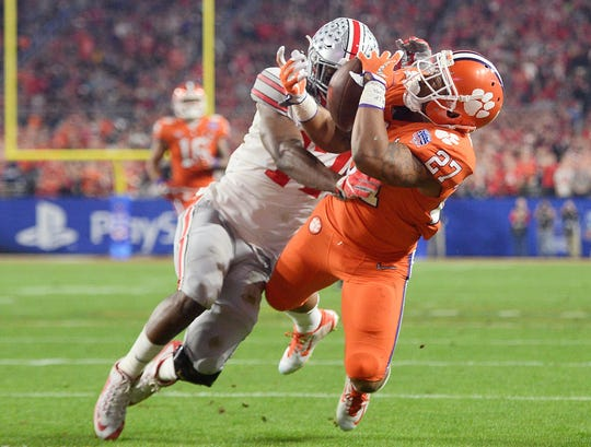 Clemson running back C.J. Fuller (27) catches a touchdown pass defended by Ohio State linebacker Jerome Baker (back) during the second quarter in the 2016 CFP semifinal at University of Phoenix Stadium.