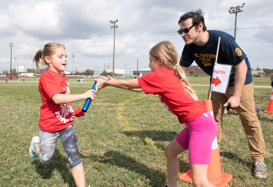 East Heights students Audryna Risley hands over the baton to Livia Dixon in a relay race during the 77th Annual Archie Riehl Rotary Field Day at North Middle Thursday, Oct. 4, 2018.