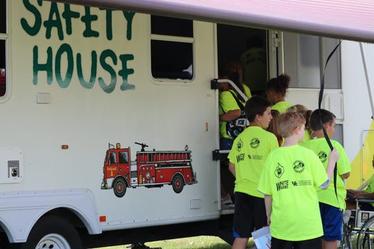 Students enter the Safety House to sit in on a session about home safety including what to do in the case of a fire.