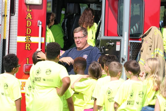 5th graders climb into the fire truck as they learn about fire safety.