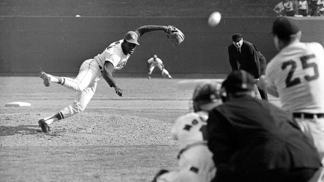 Bob Gibson, St. Louis Cardinals ace pitcher, fires the ball at Detroit Tigers first baseman Norm Cash in the ninth inning of the first game of the World Series Oct. 2, 1968, at Busch Stadium in St. Louis. Gibson struck Cash out for his 16th strikeout of the game and set a World Series record. Looking on are catcher Tim McCarver, home plate umpire Tom Gorman and first base umpire Jim Honochick.