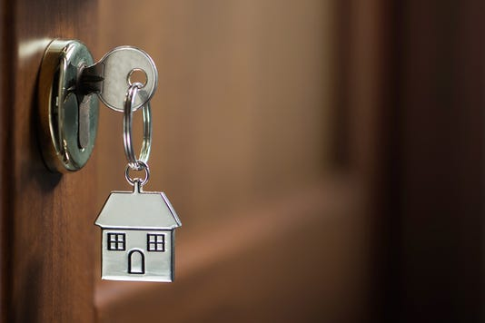 Silver House Key In A Door