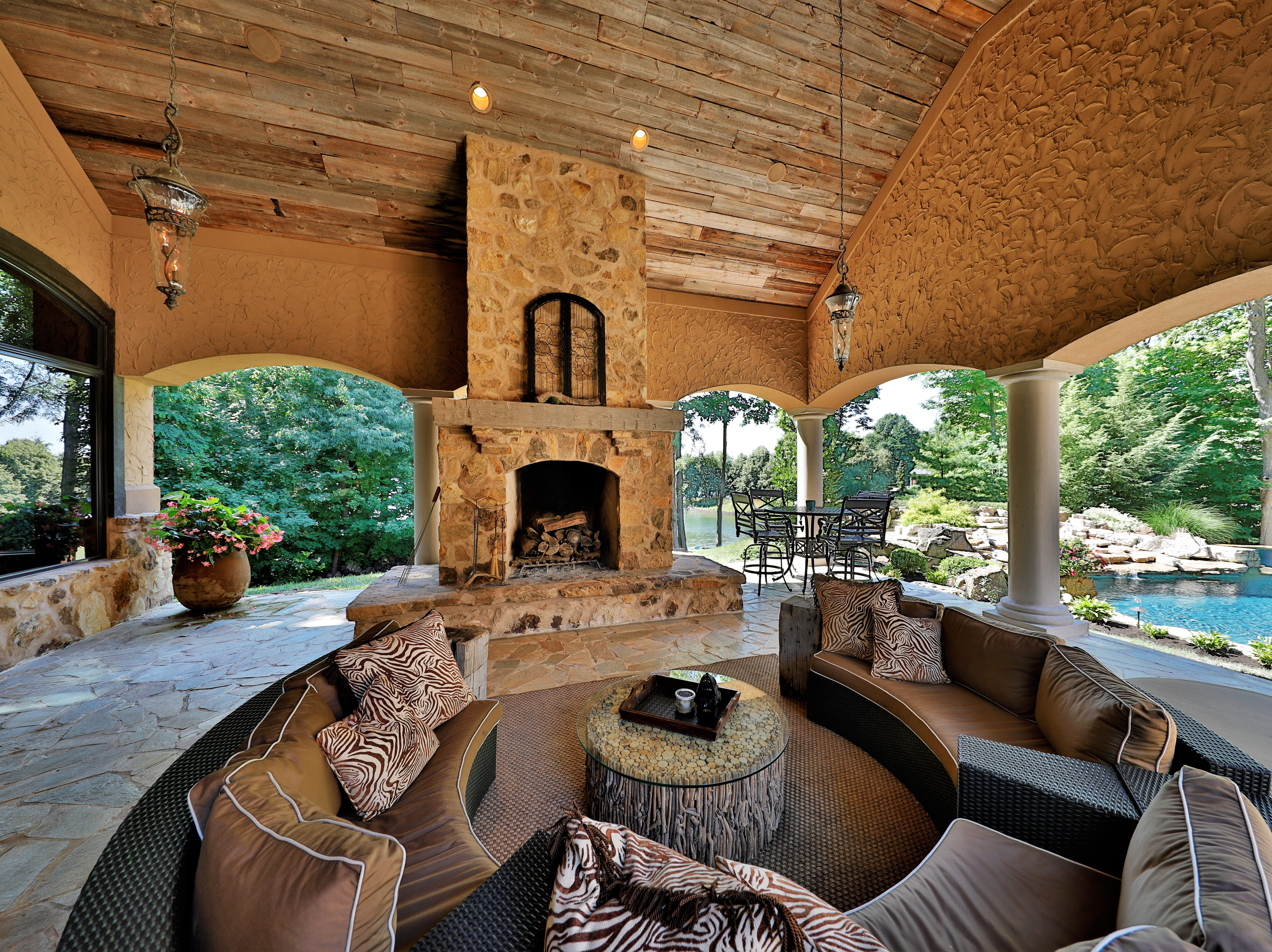 Across from the outdoor kitchen is a stone fireplace and large living area with water views.