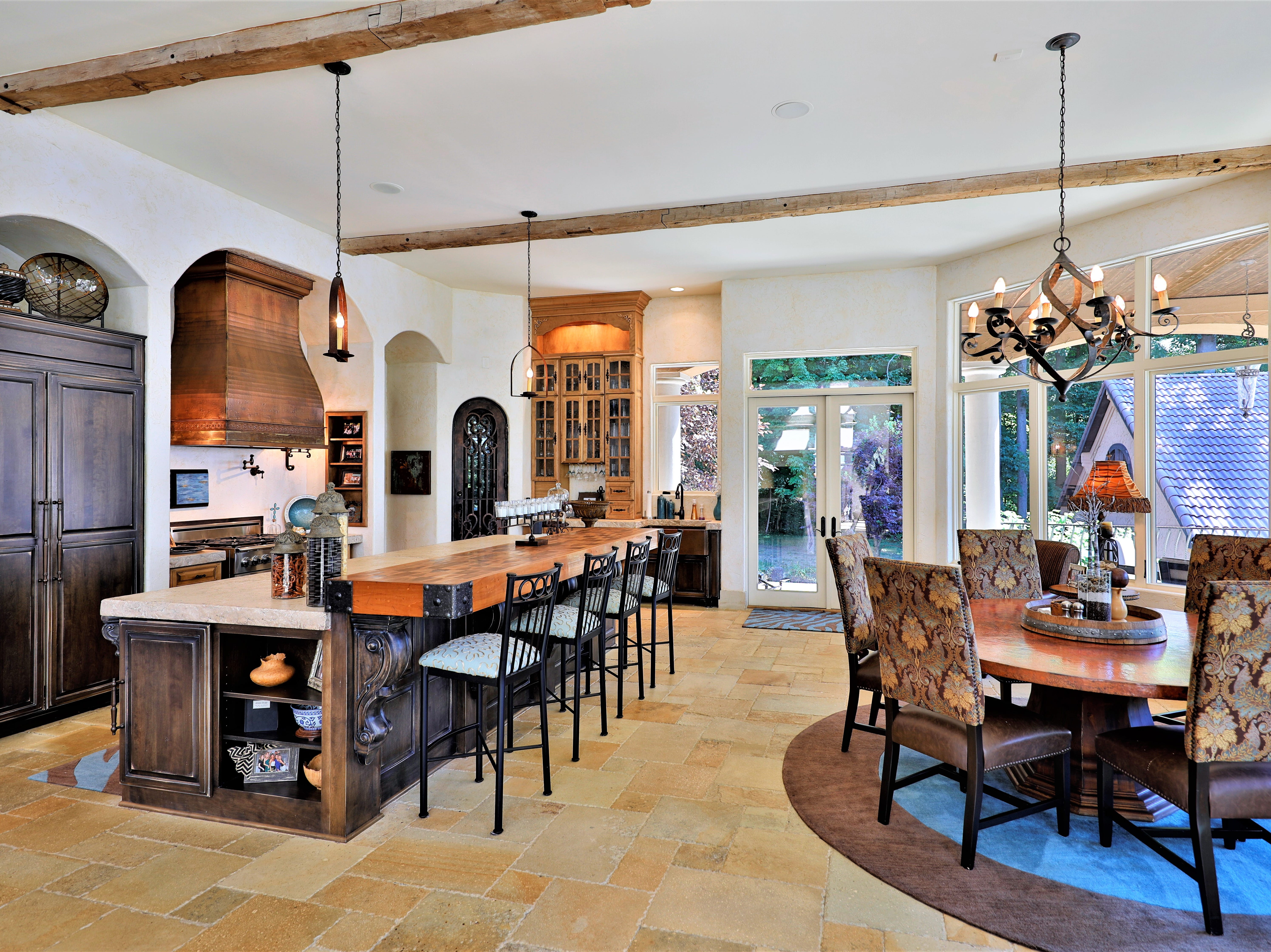 """The home's open-concept main kitchen includes a large island with a concrete counter top and breakfast nook. Through the arched door is a pantry and second """"preparatory"""" kitchen with laundry."""