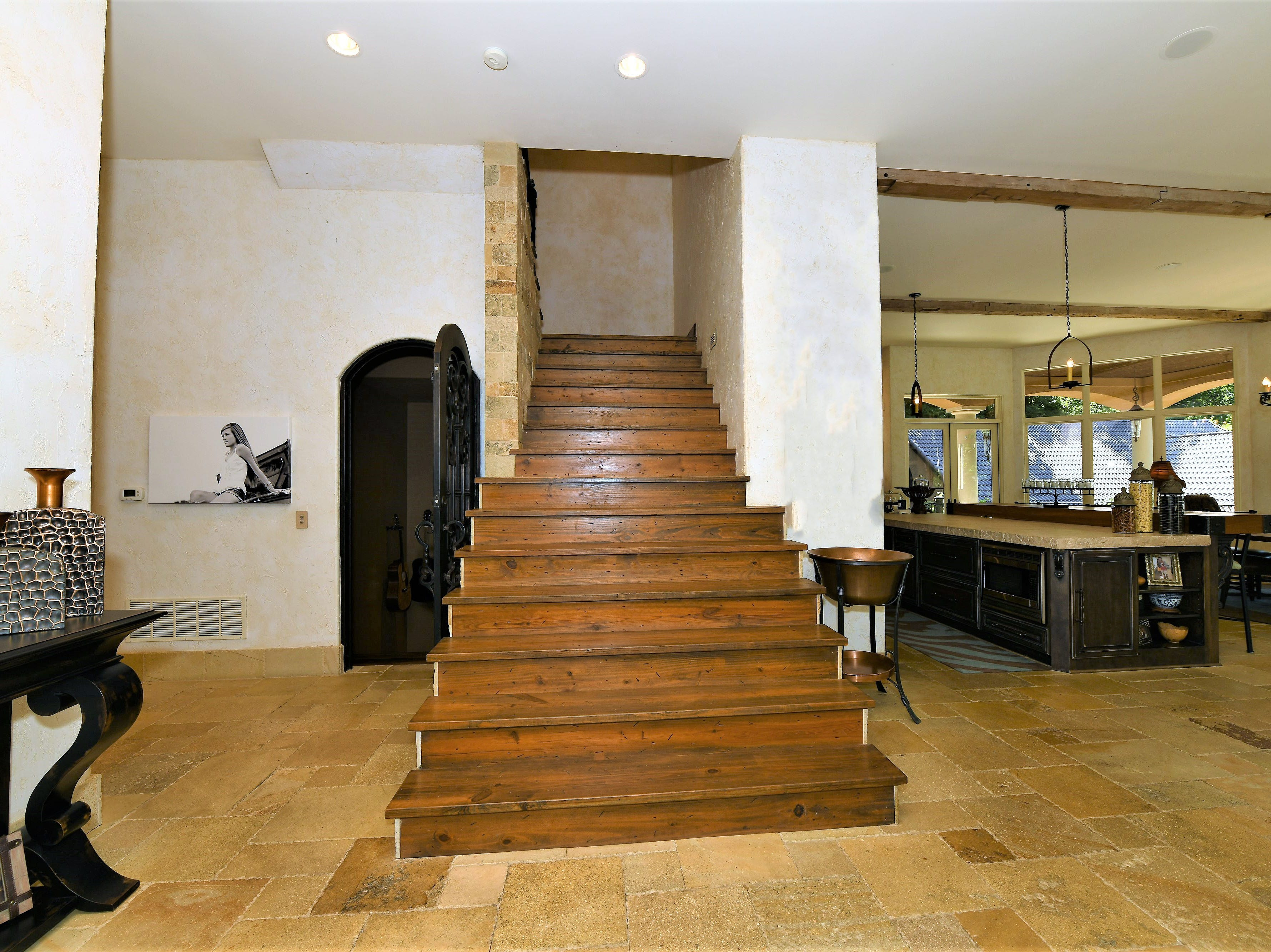 Behind the kitchen, a large wooden staircase leads to two apartment-like spaces on the second floor.