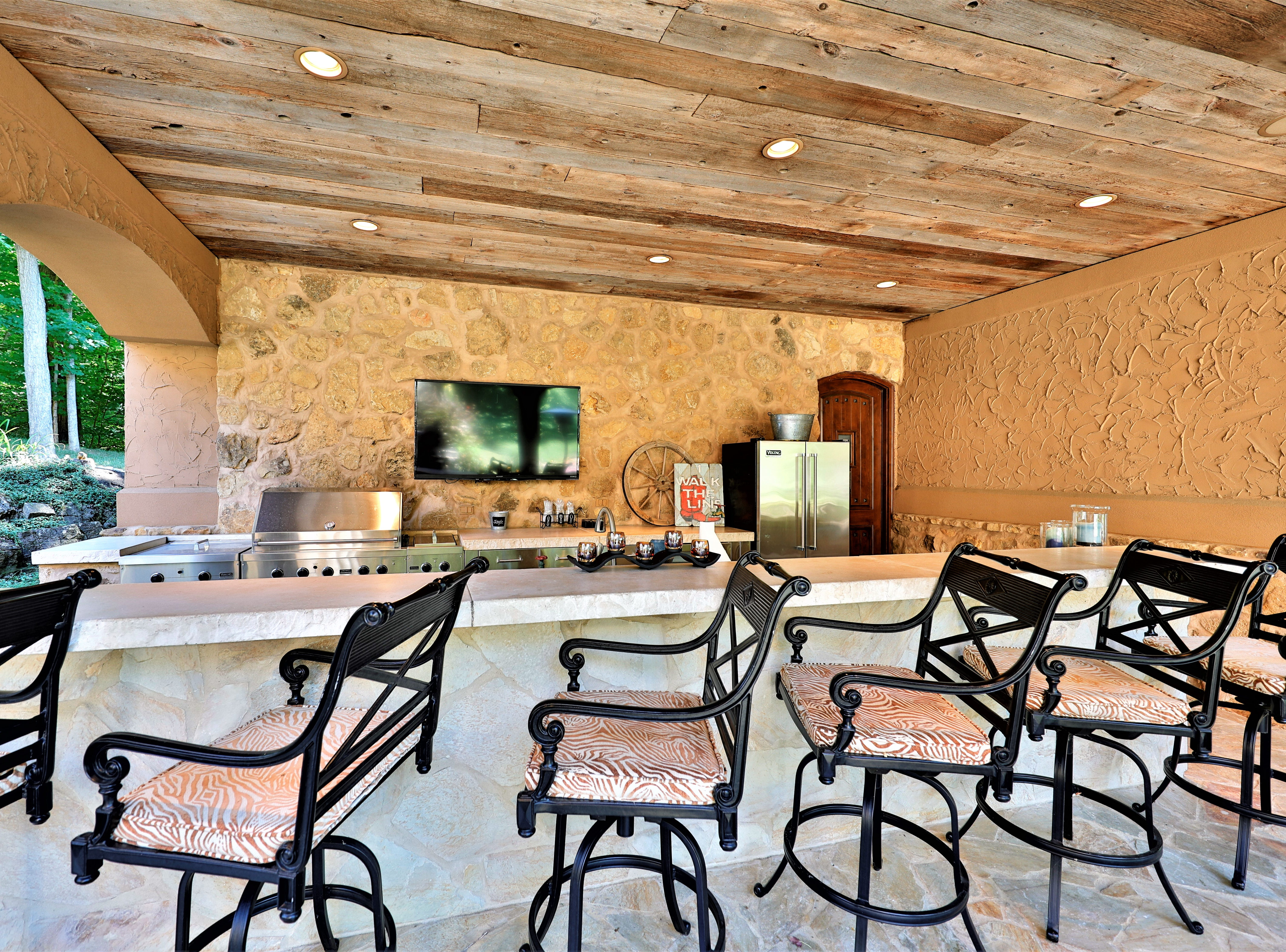 The covered patio off the pool house includes a full outdoor kitchen with a long bar that seats six.