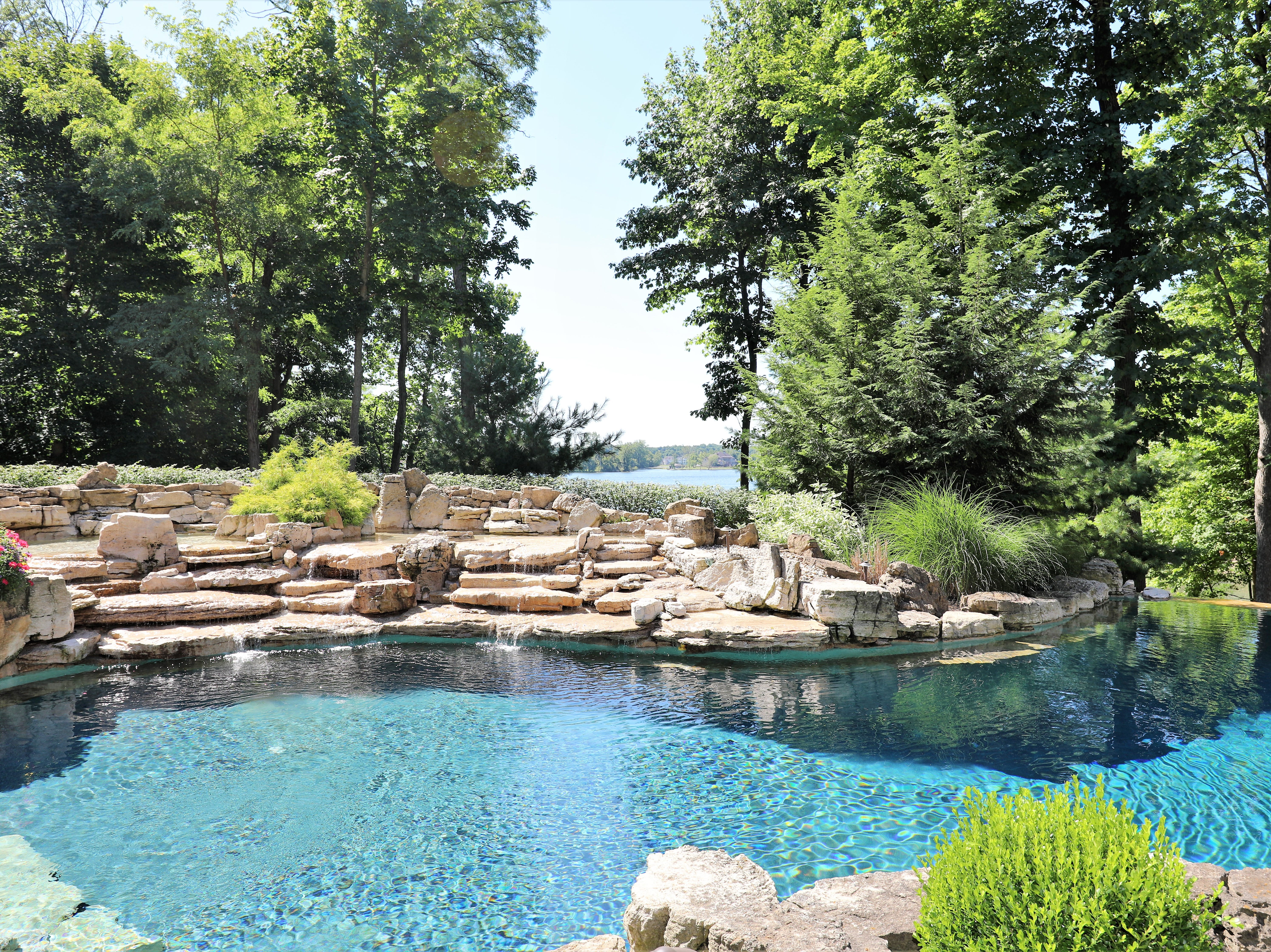 In the backyard is a pool with a rock waterfall feature that rolls down the property's slight hill towards its private reservoir access.