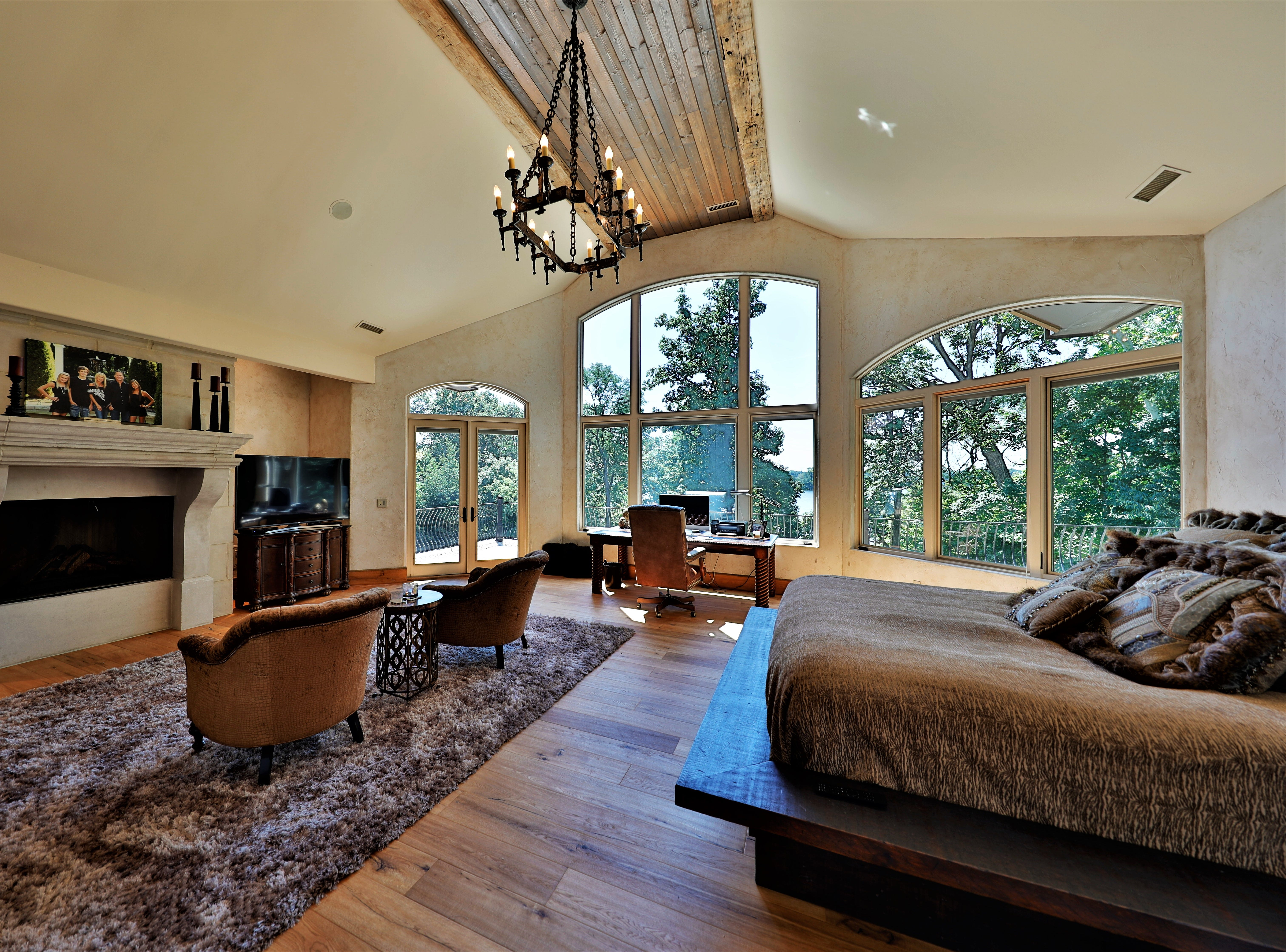 The master suite on the second floor includes floor-to-ceiling windows, a wood-burning fireplace and outdoor veranda.