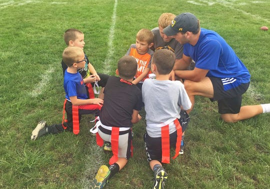 Jack Kiser (right) helps out with some of the town's kids during a flag football game.
