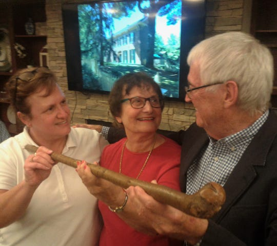 Jim Hayes accepts the gift of this cane attributed to world famous artist Grant Wood from Judy Terry and her daughter, Saira Vitosh Steen, during a recent presentation at Vintage Cooperative in Coralville.  Hayes is the owner and resident curator of the historic house Wood refurbished at 1142 East Court Street in Iowa City in the late 1930s.