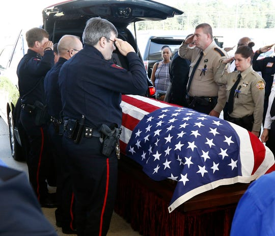 An honor guard of local lawmen and women salute as the casket of Brookhaven Police Corporal Zach Moak is loaded into a hearse following funeral services Thursday, Oct. 4, 2018, at Easthaven Baptist Church in Brookhaven, Miss.