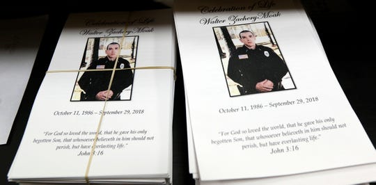 Funeral programs with a photograph of Corporal Zach Moak await distribution at funeral services Thursday, Oct. 4, 2018, for the Brookhaven, Miss., police officer.
