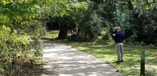 On Thursday, Oct. 4, 2018, a Knoxville Police Department officer examines the Ten Mile Greenway, where Werner Stierle was attacked on Sept. 29.