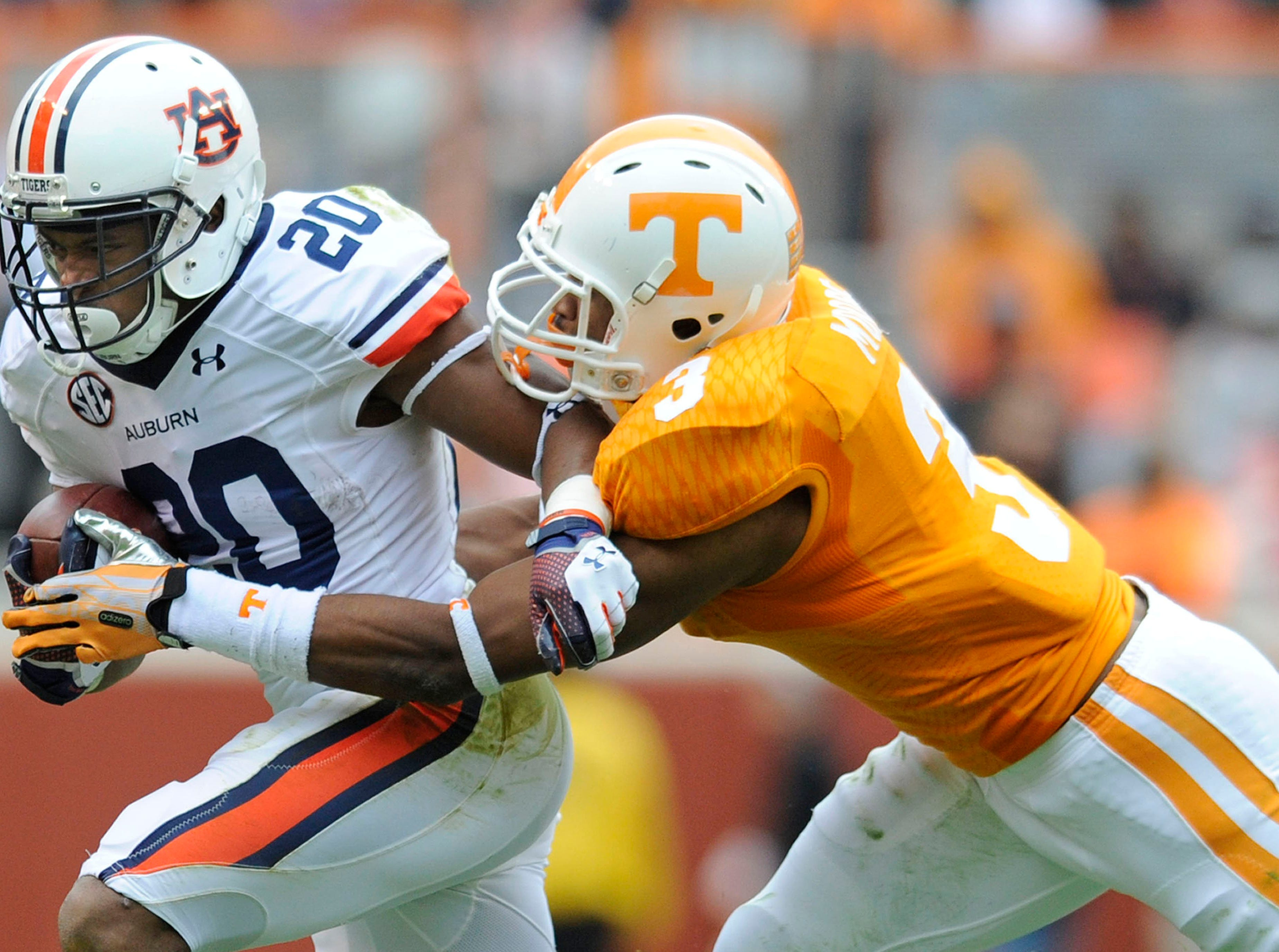 Auburn running back Corey Grant (20) fends off a tackle from Tennessee defensive back Byron Moore (3) during the second half against Auburn at Neyland Stadium in Knoxville on Saturday, Nov. 9, 2013.