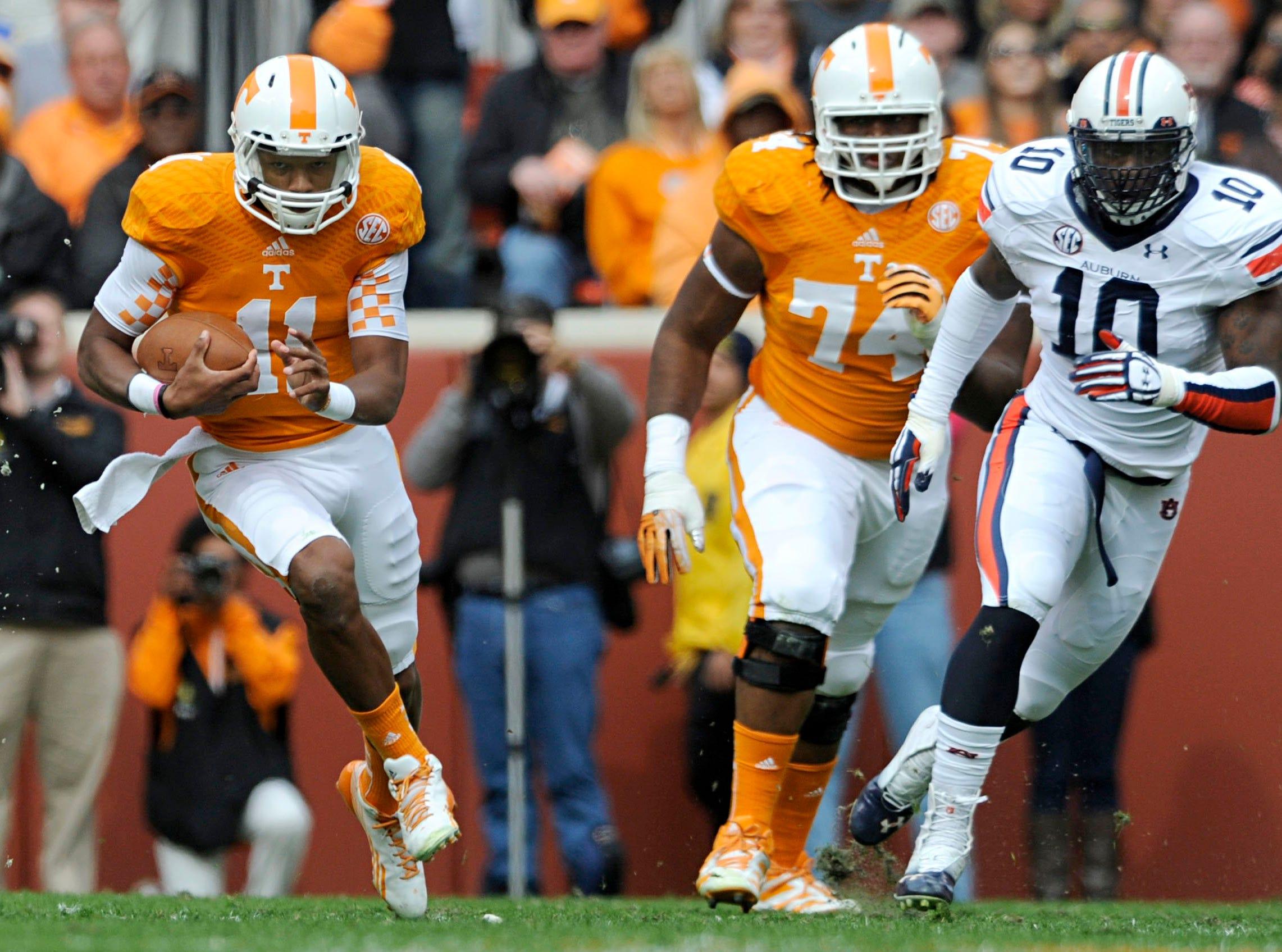 Tennessee quarterback Joshua Dobbs (11) runs downfield past Auburn defensive end LaDarius Owens (10) during the first half at Neyland Stadium in Knoxville on Saturday, Nov. 9, 2013.