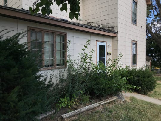 Weeds and overgrown shrubs, as well as a black ring around the outside walls where it meets the roof are visible from the outside of 400 N. Salisbury St. City inspectors found 45 violations inside the house.