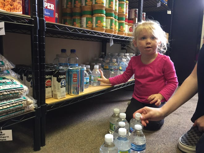 Evalynn McMahan, 2, helps stock food pantry shelves at Bountiful Harvest in Brighton, a nonprofit her great-grandmother Yvonne Cavalli founded, seen on Thursday, Oct. 4, 2018.
