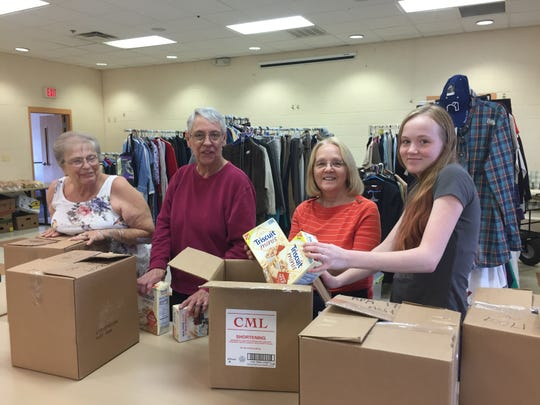 From left, Bountiful Harvest founder Yvonne Cavalli boxes up donated food with volunteers Connie Therrien, Irene Gauthier and Ella Gautheir at the Brighton Community Center, Thursday, Oct. 4, 2018.