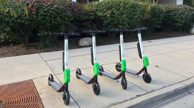 Electric scooters, available for rent through a tech company called Lime, are lined up outside the downtown Lansing branch of the Capital Area District Library on Thursday, October 4, 2018.