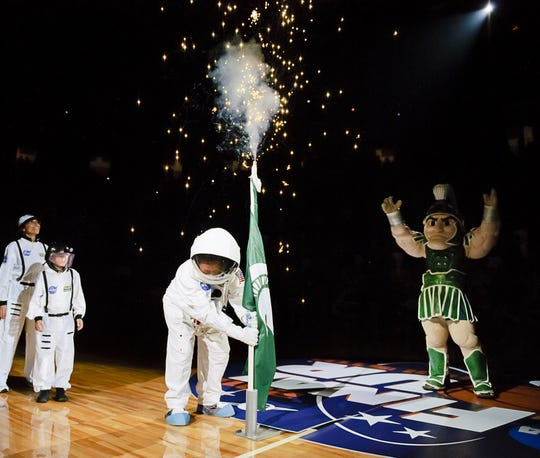MSU Men's Basketball head Coach Tom Izzo (center) plants a State flag at center court while wearing a space suit during Midnight Madness Friday October 15, 2010 in East Lansing.  The Final four this season will be held in Houston, the home of NASA. KEVIN W. FOWLER PHOTO