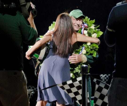 MSU Men's Basketball Head Coach Tom Izzo (right) is hugged by his wife Lupe in the Winner's Circle after driving the MSU College of Engineering race car onto the floor during  the MSU basketball Midnight Madness event Friday October 16, 2009 at the Breslin Center in East Lansing.