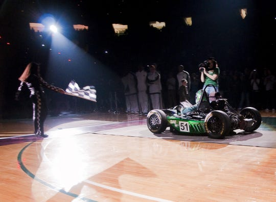 """MSU Men's Basketball Head Coach Tom Izzo drives the MSU College of Engineering race car on to the floor during """"Celebrate the Moment,"""" the MSU basketball Midnight Madness event Friday October 16, 2009 at the Breslin Center in East Lansing."""