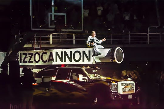 MSU Men's Basketball Head Coach Tom Izzo rides out to greet the crowd on a cannon during Michigan State Madness Friday October 18, 2013 at the Breslin Center in East Lansing.  The crowd was lead to believe that Izzo would be shot out of it across the court and into a net.  Instead Jennifer Smith-Schneider was the dare devil.