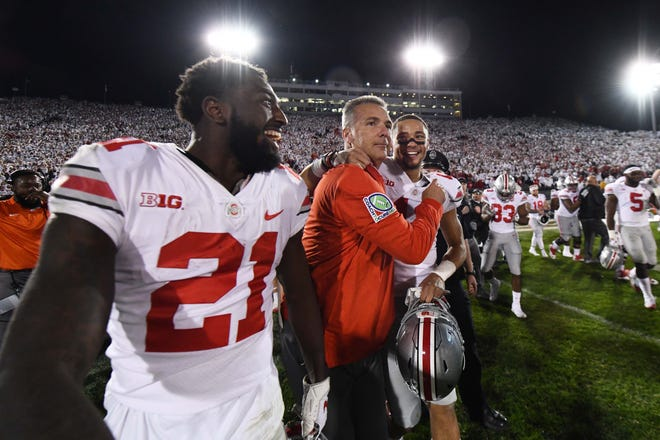 Ohio State coach Urban Meyer leaves the field flanked by Parris Campbell (21) and Austin Mark after the come-from-behind 27-26 win at Penn State. It was one week after a similar big victory against Penn State that the 2017 Buckeyes lost to Iowa.