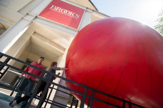 April 28, 2016 - Stanton Thomas (left) and Kip Peterson take turns punching a giant inflatable ball made for the RedBall Project by aritst Kurt Perschke as it sits wedged in front of the Memphis Brooks Museum of Art. Perschke's creation has travelled the globe, and will spend ten days in Memphis, being stuffed into different locations around the city each day from the New Daisy Theatre to the Stax Museum. (Brandon Dill/Special to The Commercial Appeal)