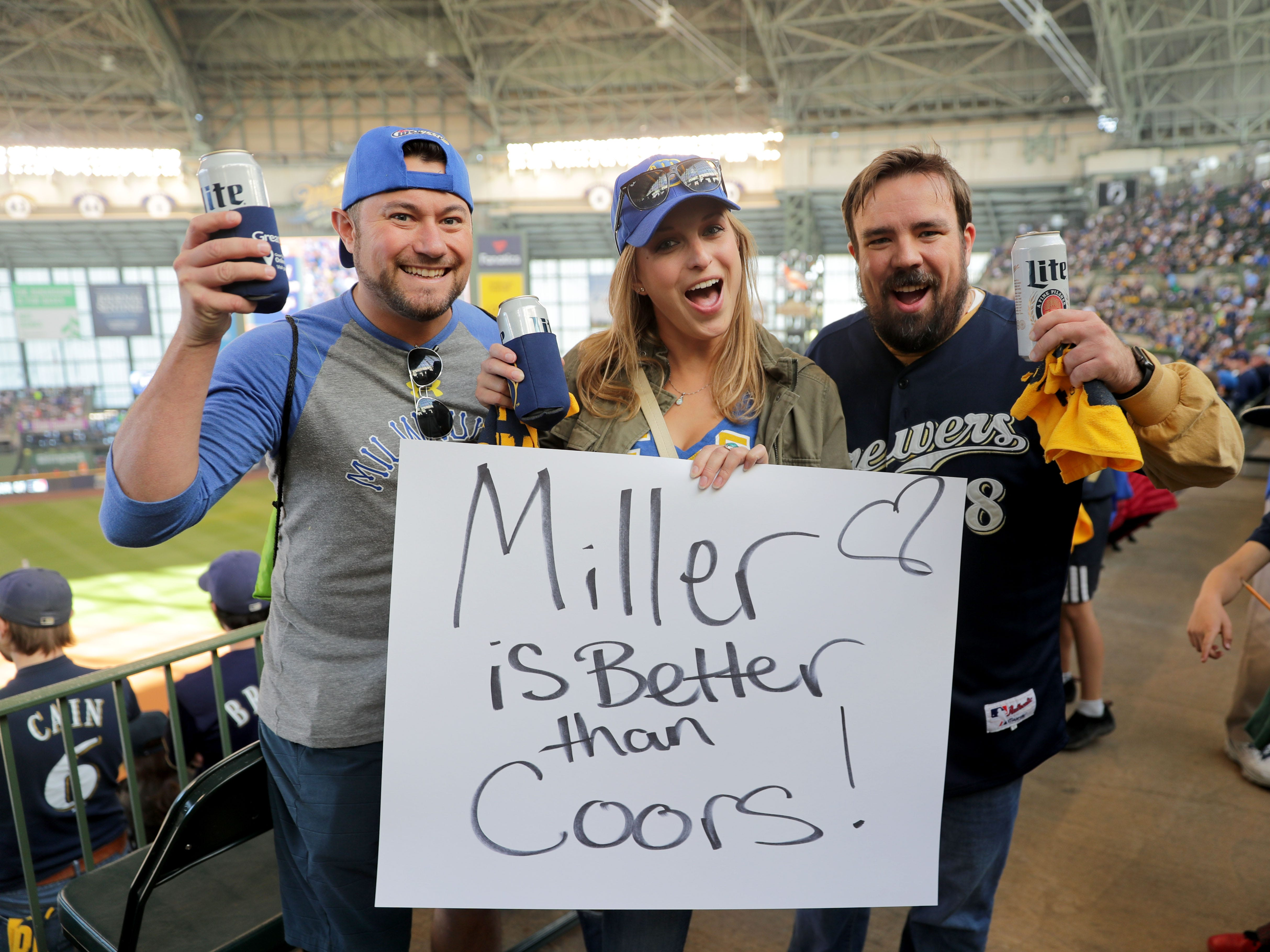 Ashley Poull (center), with Kevin Heidorn (left) and Kyle Kasbohm, all of Milwaukee, holds a sign showing what beer she favors before the Milwaukee Brewers' National League Division Series game against the Colorado Rockies.