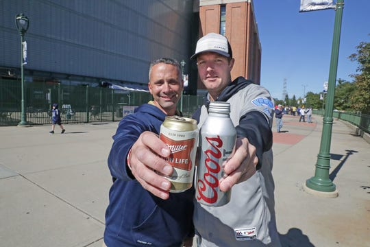 Joe Citro of Cudhay holds a can of Miller High Life as Matt Meeusen of Pewaukee holds a Coors Light on Thursday before the Milwaukee Brewers' National League Division Series game against the Colorado Rockies.