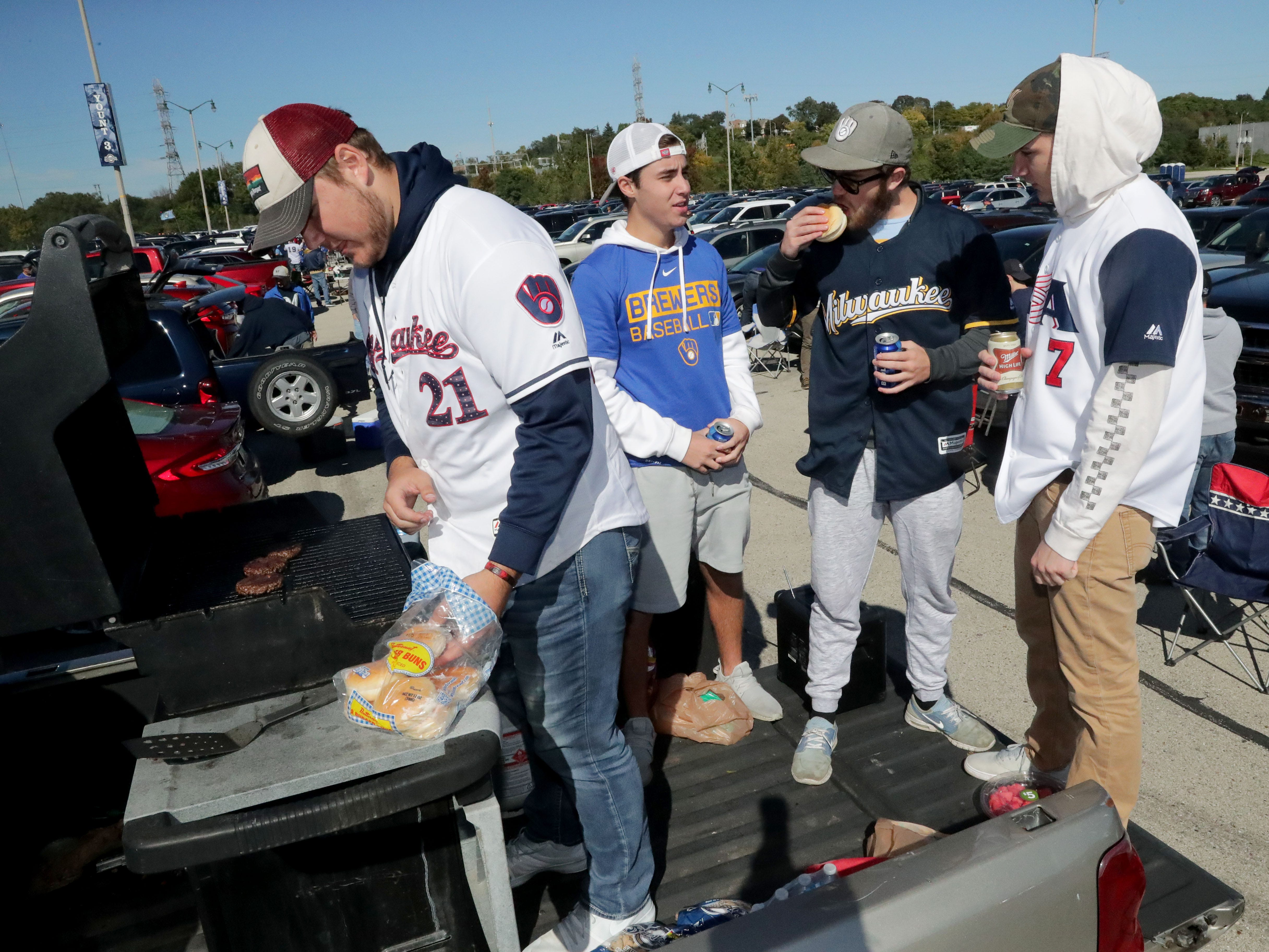 Brewers fans Parker Theel (from left), Stathis Demopoulos, Anthony Pascutti and Joey Glembocki, all of  Muskego, tailgate from the back of Theel's pickup truck before the Milwaukee Brewers' National League Divisional Series game against the Colorado Rockies on Thursday.