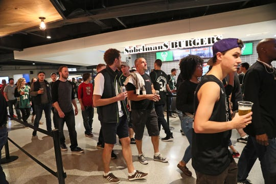 Fans walk through the concourse at the new Fiserv Forum before the Bucks' preseason opener against the Bulls.