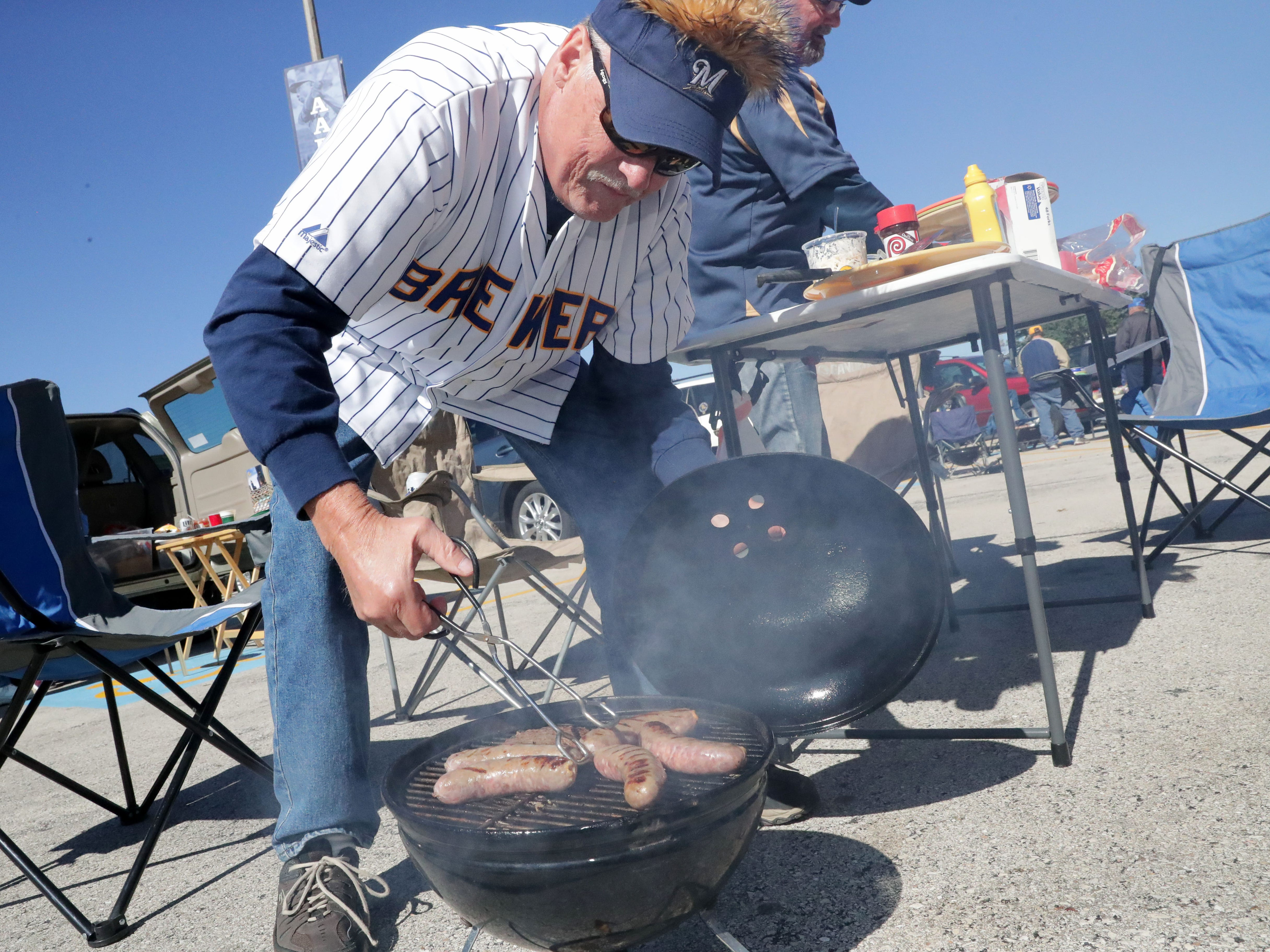 Skeeter Fehly of Fort Atkinson grills brats before the Milwaukee Brewers National League Divisional Series game against the Colorado Rockies.