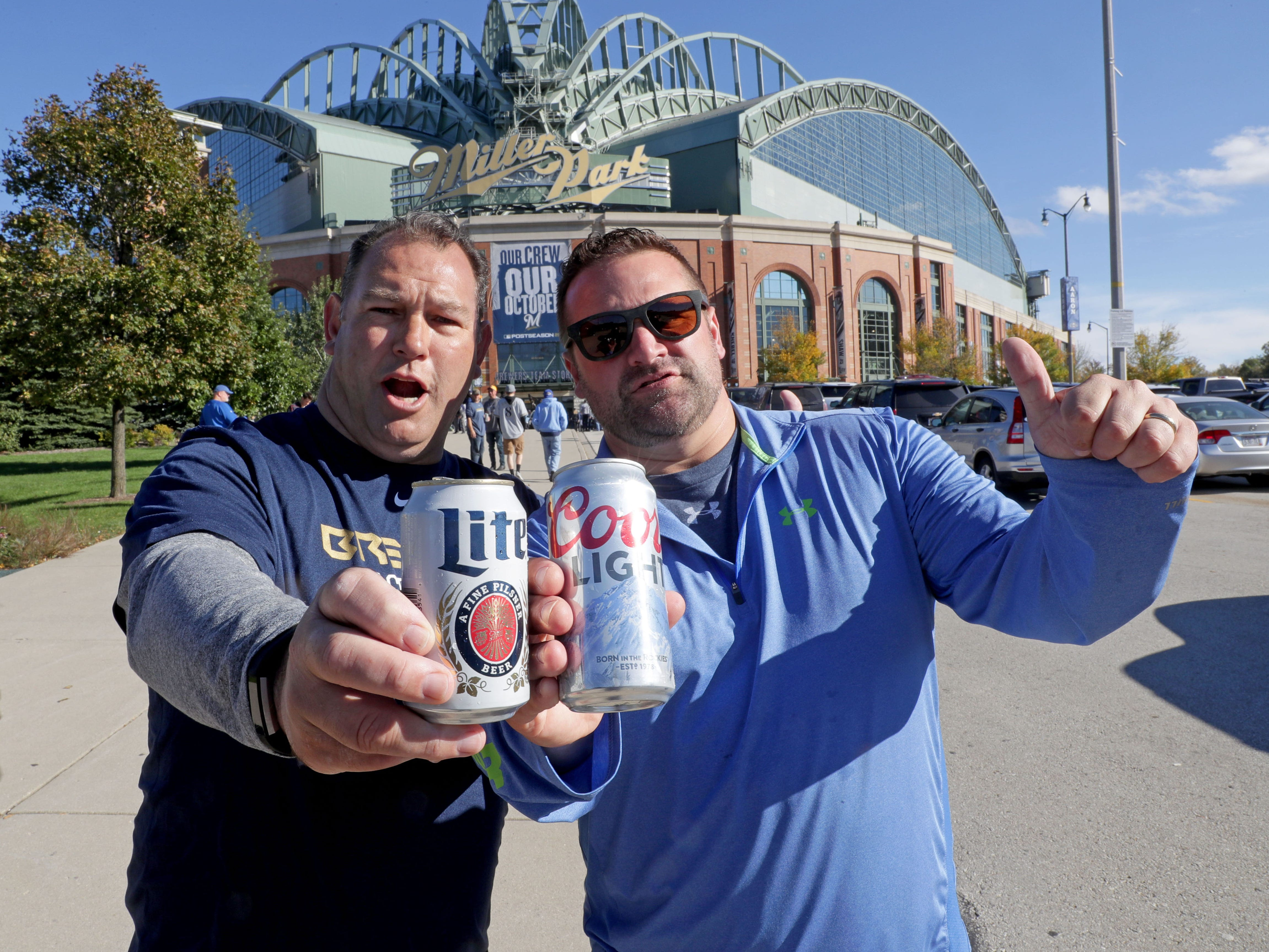 Wayne Morgan (left) of Mequon holds a can of Miller Lite as his friend Jeremy Lueloff of Port Washington holds a can of Coors Light before the game Thursday.
