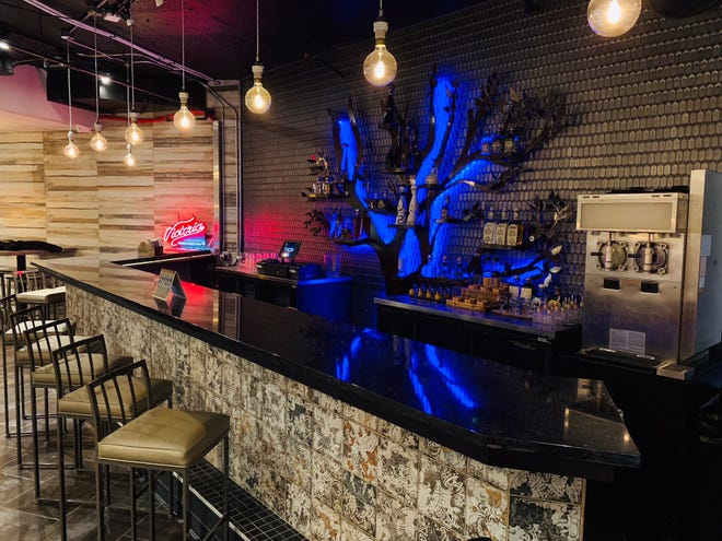 The blue light behind the bar at Taco Bar, 782 N. Jefferson St., is a metal tree sculpture that holds various tequillas, including high-end ones for sipping.