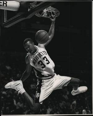 Former Marquette player Ron Curry throws down a slam dunk in 1992.