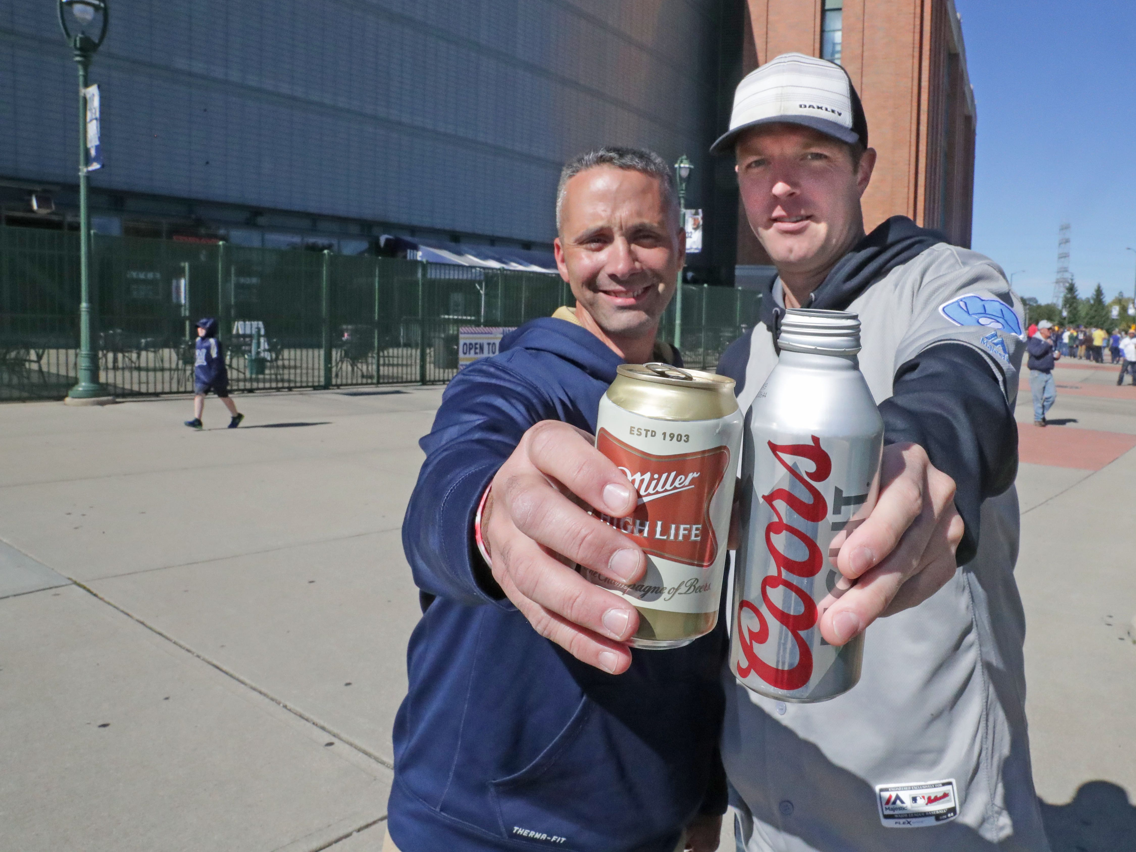 Joe Citro of Cudhay holds a can for Miller High Life as Matt Meeusen of Pewaukee  holds a Coors Light before the Milwaukee Brewers National League Divisional Series game against the Colorado Rockies.