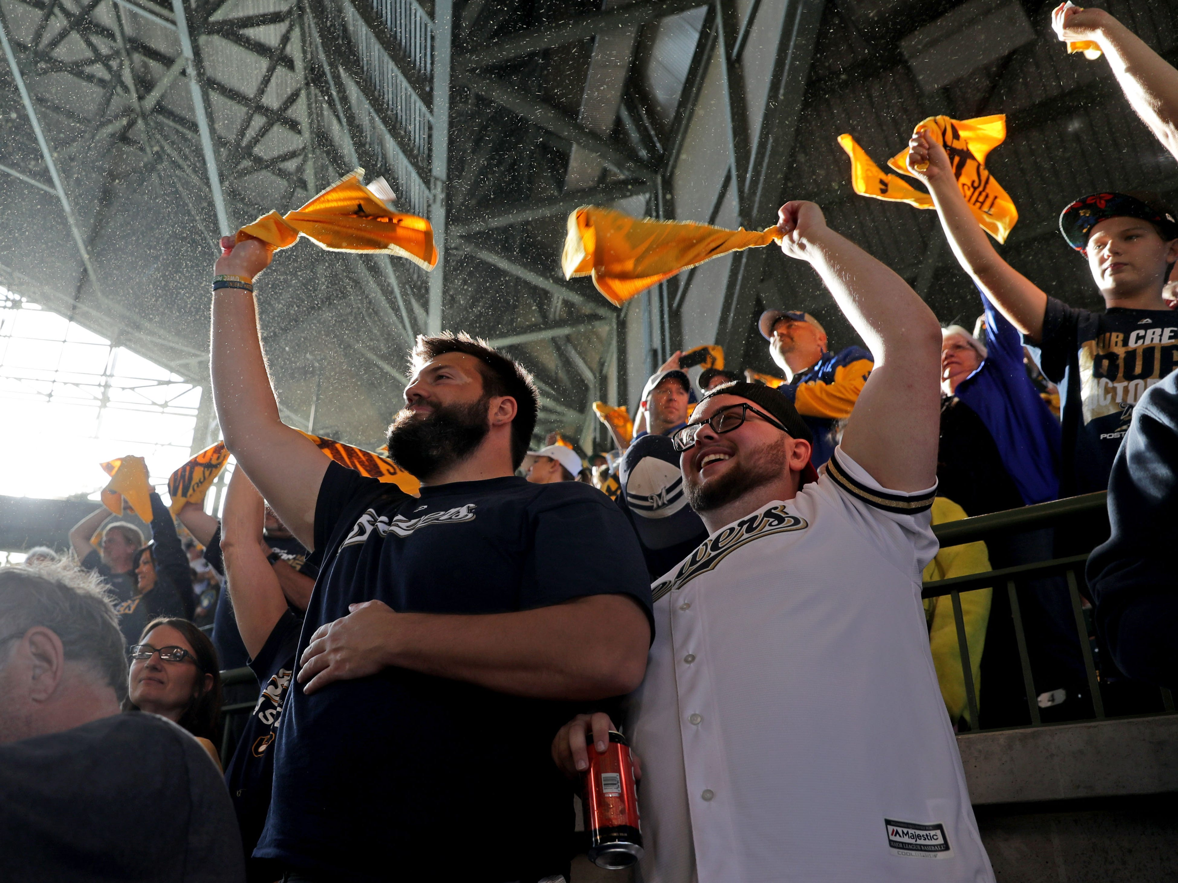 Mathew Riedel (left) and Hunter Halverson, both of Eau Claire, wave their towels before the Milwaukee Brewers' National League Divisional Series game against the Colorado Rockies on Thursday.
