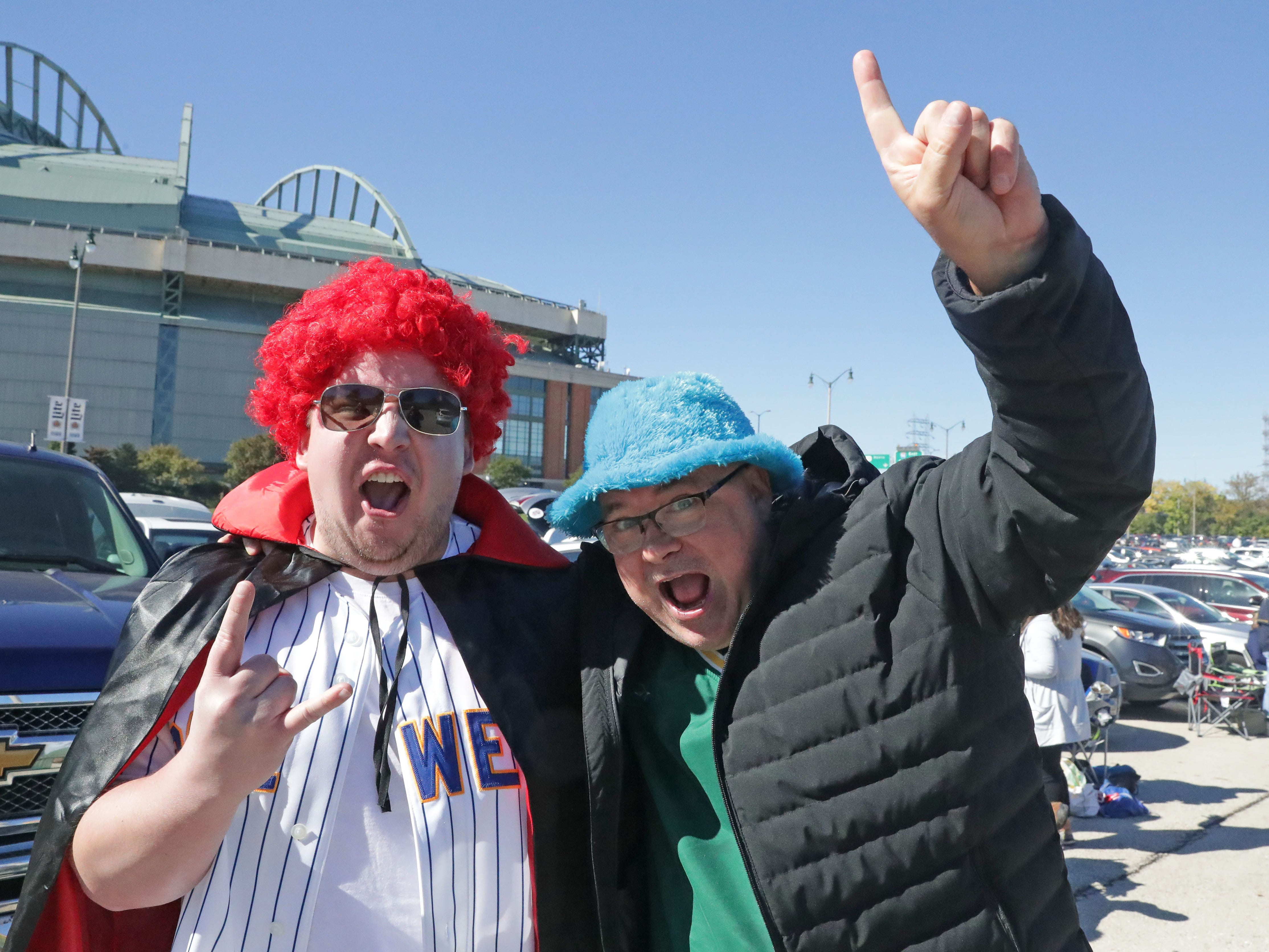 Brian Wilson (left) of Wales and Nick Laskowski of Milwaukee don a red wig and flashy blue hat while tailgating before the Milwaukee Brewers National League Divisional Series game against the Colorado Rockies.