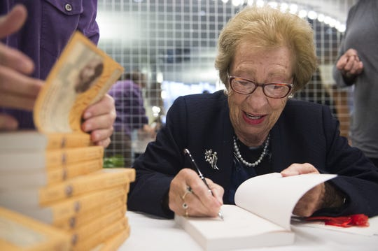 "Eva Schloss, a Holocaust survivor and stepsister of Anne Frank, smiles while signing copies of her book ""Eva's Story"" before speaking in the Knoxville Civic Auditorium on Tuesday, Feb. 21, 2017."