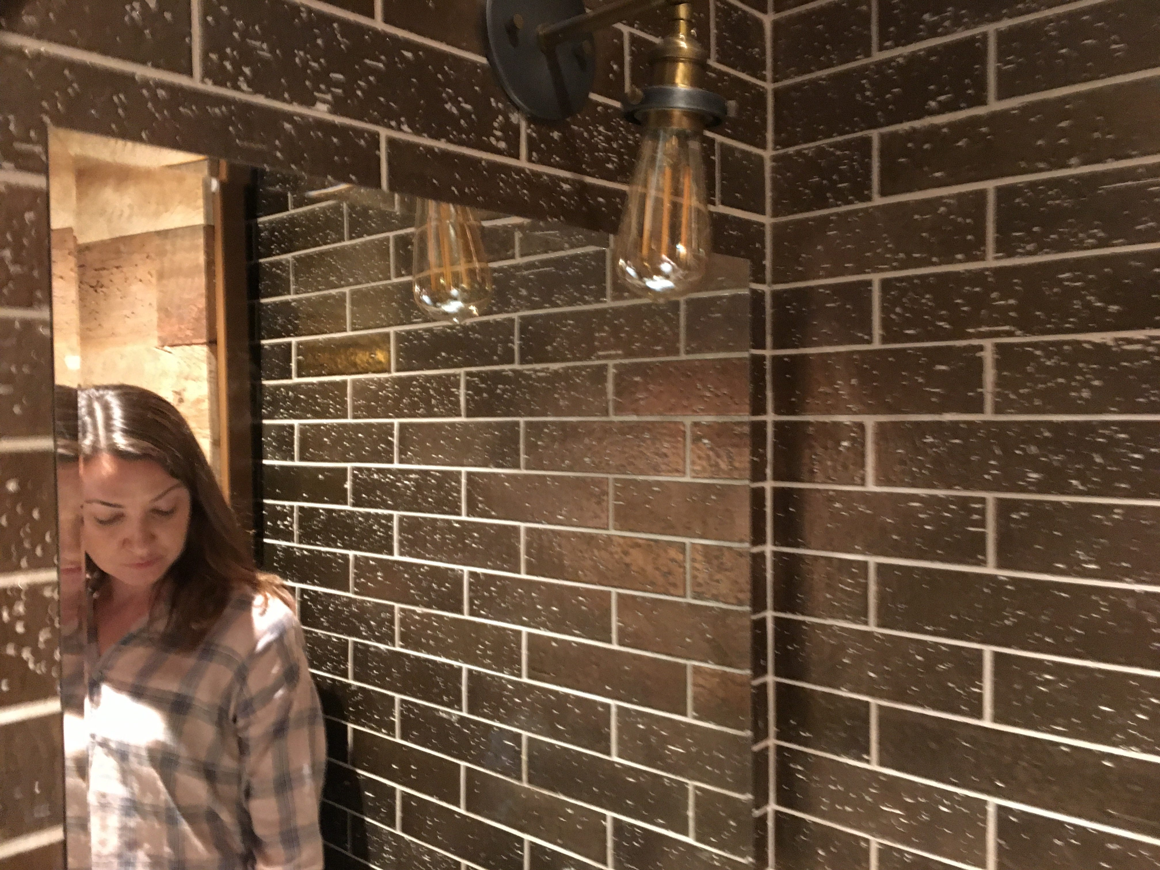 Mirror and light fixture in one of the unisex bathrooms at the Bobby Hotel downtown