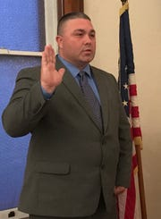 New Kirkersville Police Chief Jason Harget takes the oath of office from Mayor Terry Ashcraft during Wednesday night's village council meeting.
