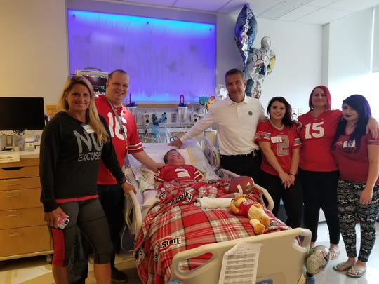 Matthew Offers, center, was visited by Ohio State Football Coach Urban Meyer and his wife, Shelley. Offers, 9, was a huge OSU fan. He died Sept. 16 after living his whole life a heart defect.