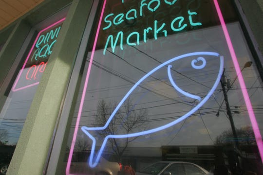 Neon signs in the storefront window advertise fresh food at Seafood Gourmet in downtown Maywood.